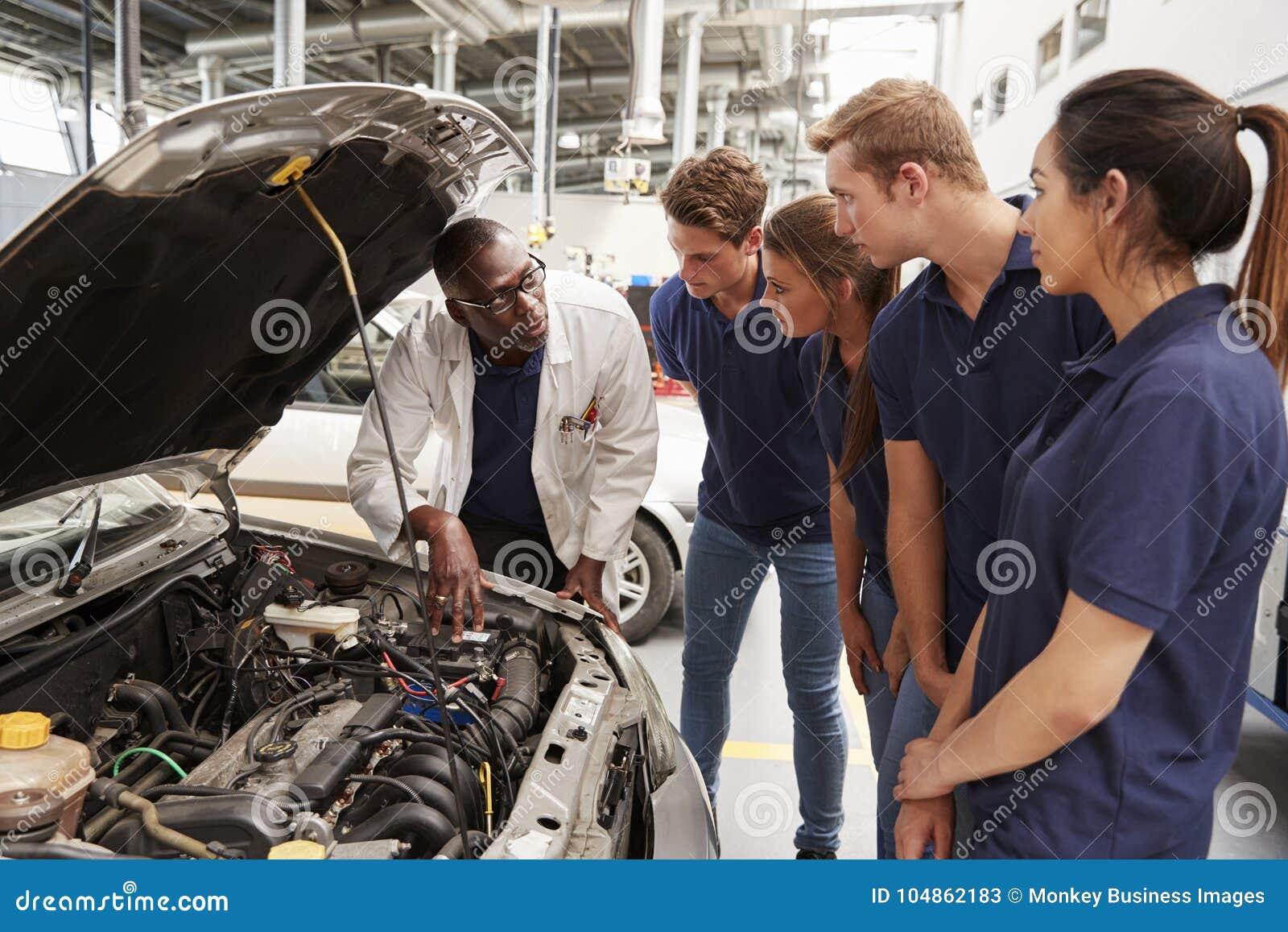 Werktuigkundige die stagiairs instrueren rond de motor van een auto