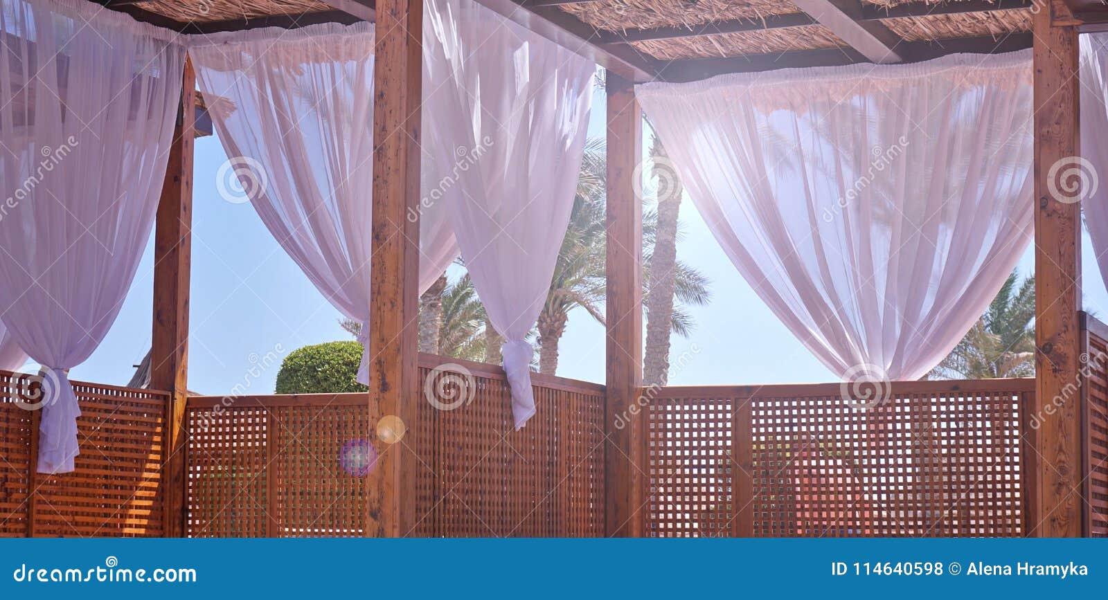 Werpt het afbaarden van met stof af witte gordijnen op de kustwind in de wind