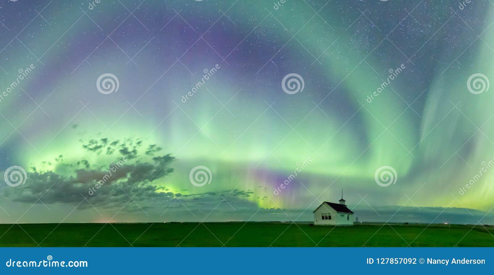 Werveling van Aurora Borealis Northern Lights over de historische Landende school Noord- van Saskatchewan