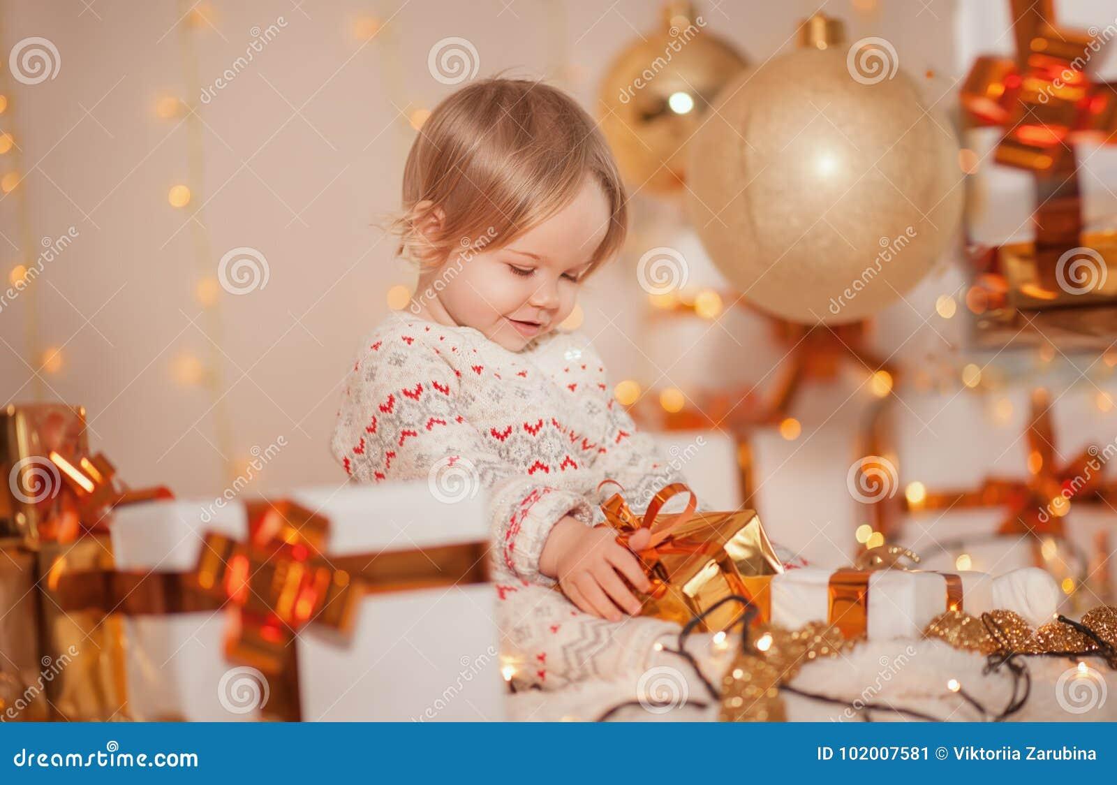 Wesoło boże narodzenia i Szczęśliwi wakacje! Mały śliczny dzieciak dziewczyny obsiadanie w dekorującym izbowym mienie teraźniejsz