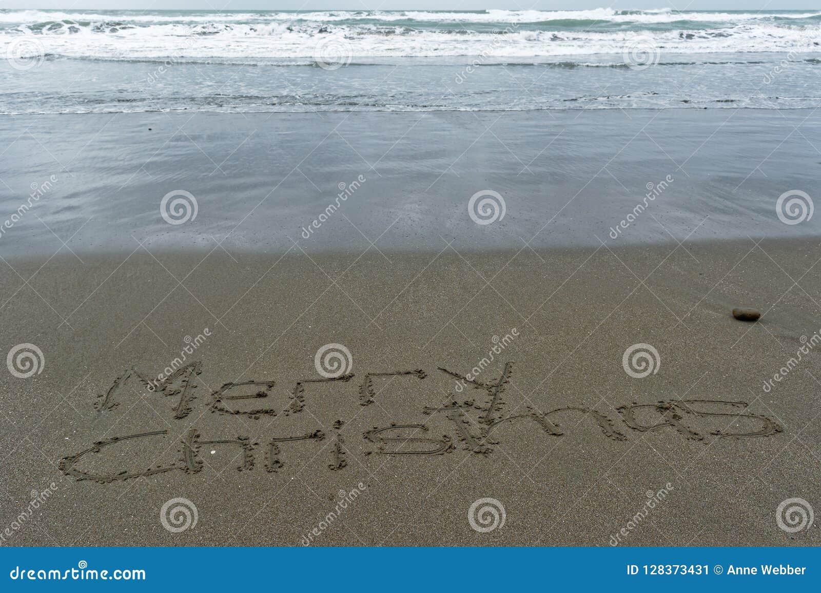 Wesoło boże narodzenia pisać w piasku z mokrym piaskiem behind