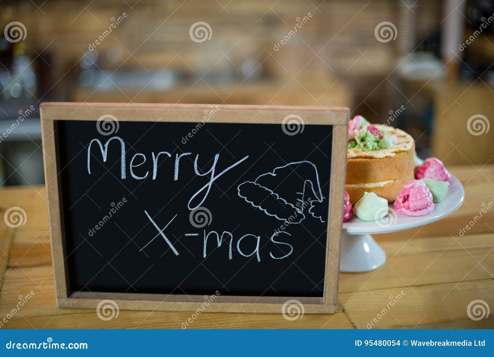 Wesoło x mas znaka deska z tortem przy kontuarem