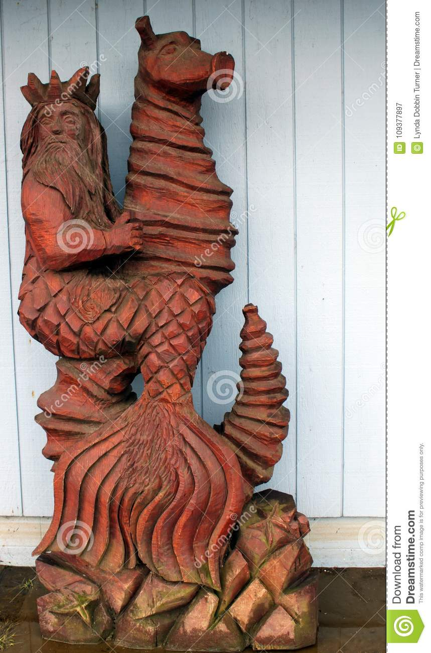 Chainsaw carving of zeus riding a sea horse editorial photography
