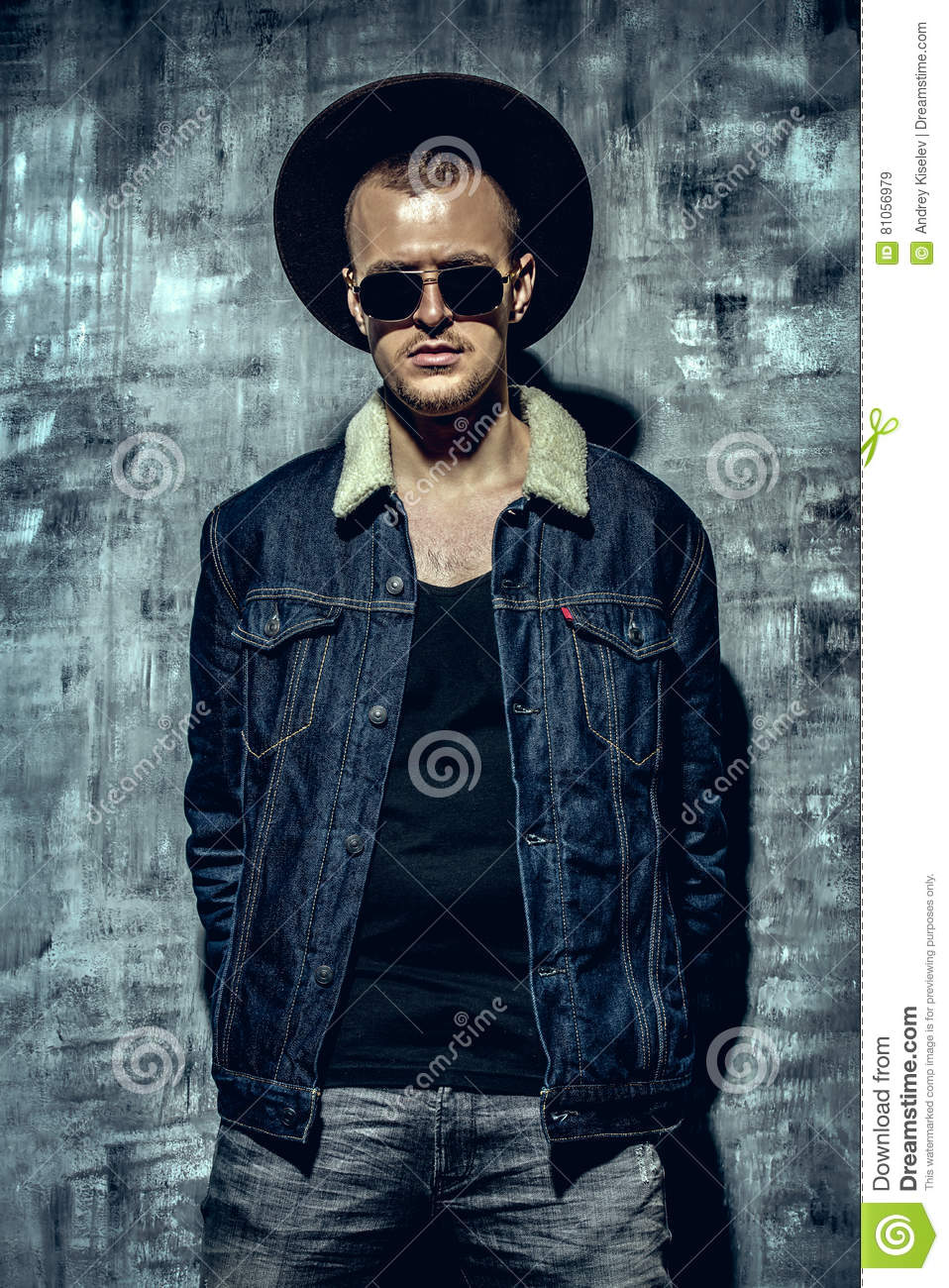 Stylish brutal man wearing jeans clothes and sunglasses posing over grunge  background. Denim collection. Male fashion. 296487d00c9c