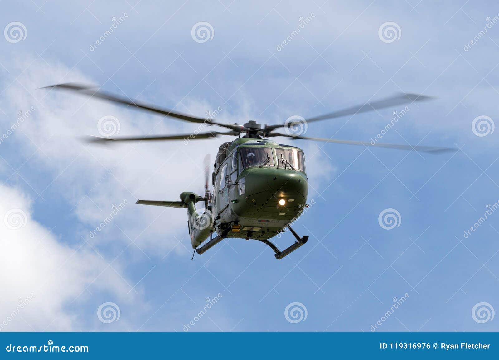 Westlandlynx AH 7 helikopter XZ184 van de Britse Korpsen die van de Legerlucht tegen een gedeeltelijk bewolkte hemel vliegen