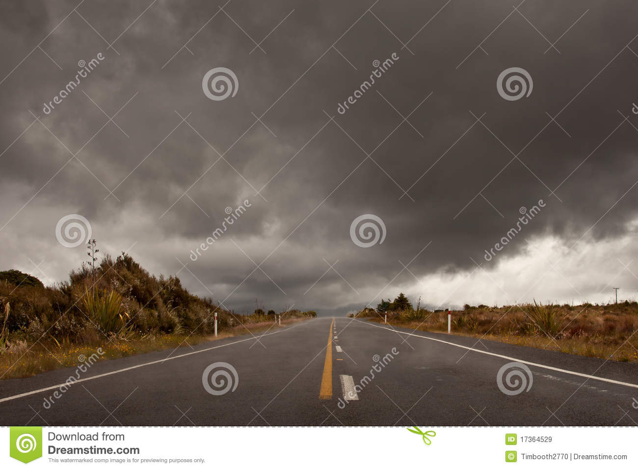 Wet road leading into a storm cloudy sky