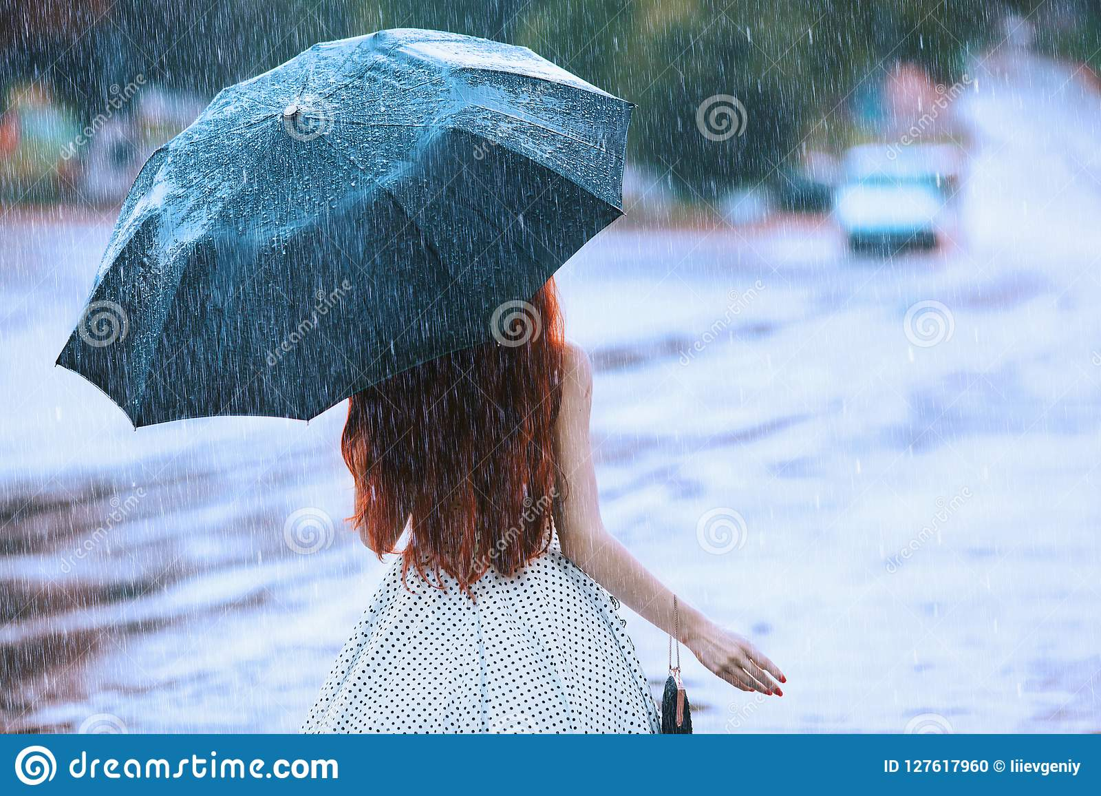 Wet weather. Autumn rain. Lonely girl in polka dots dress hold black umbrella. Raining in city. Wet umbrella against the backdrop