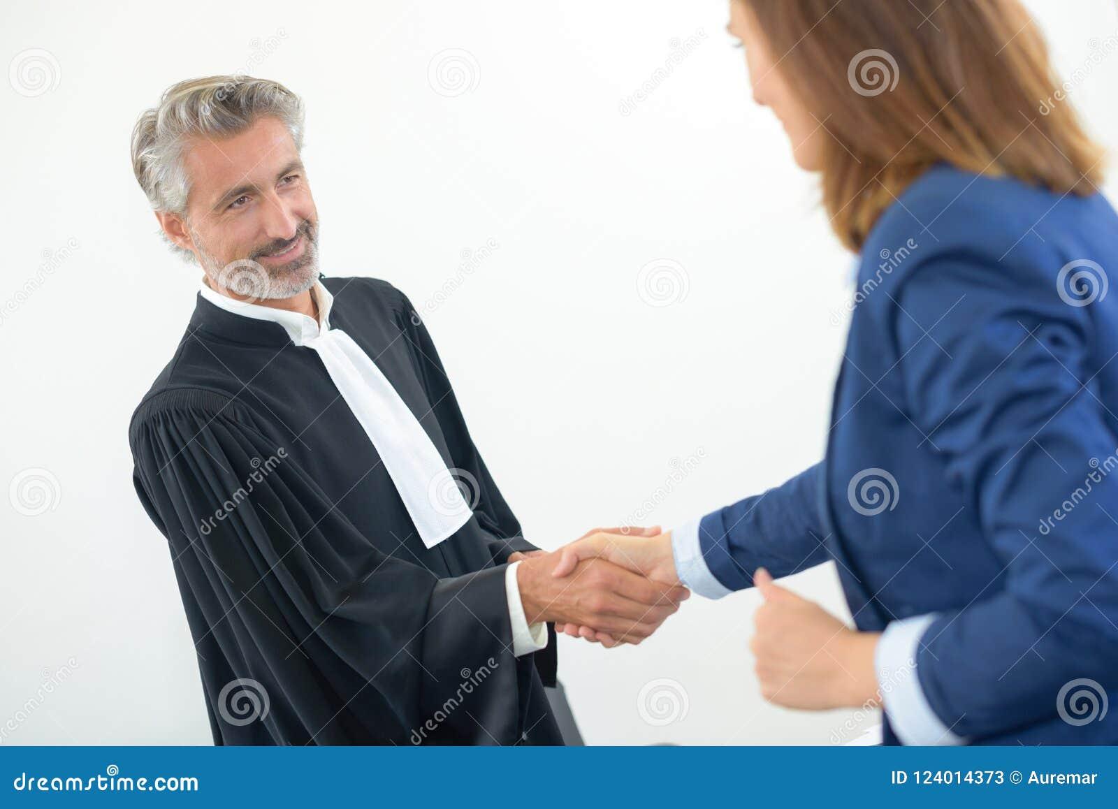 Wettelijke arbeider die in robes handen met vrouw in kostuum schudden