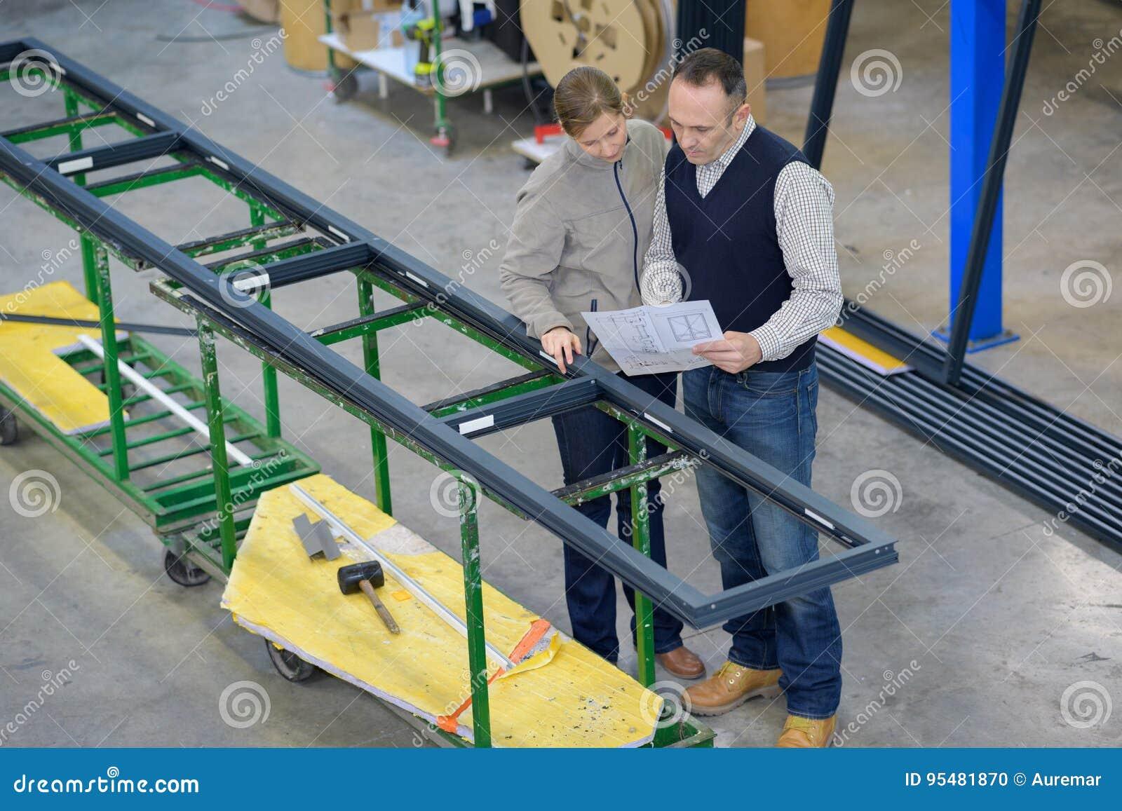 Wewnętrzna ruchliwie fabryka z personelem przy prac ławkami