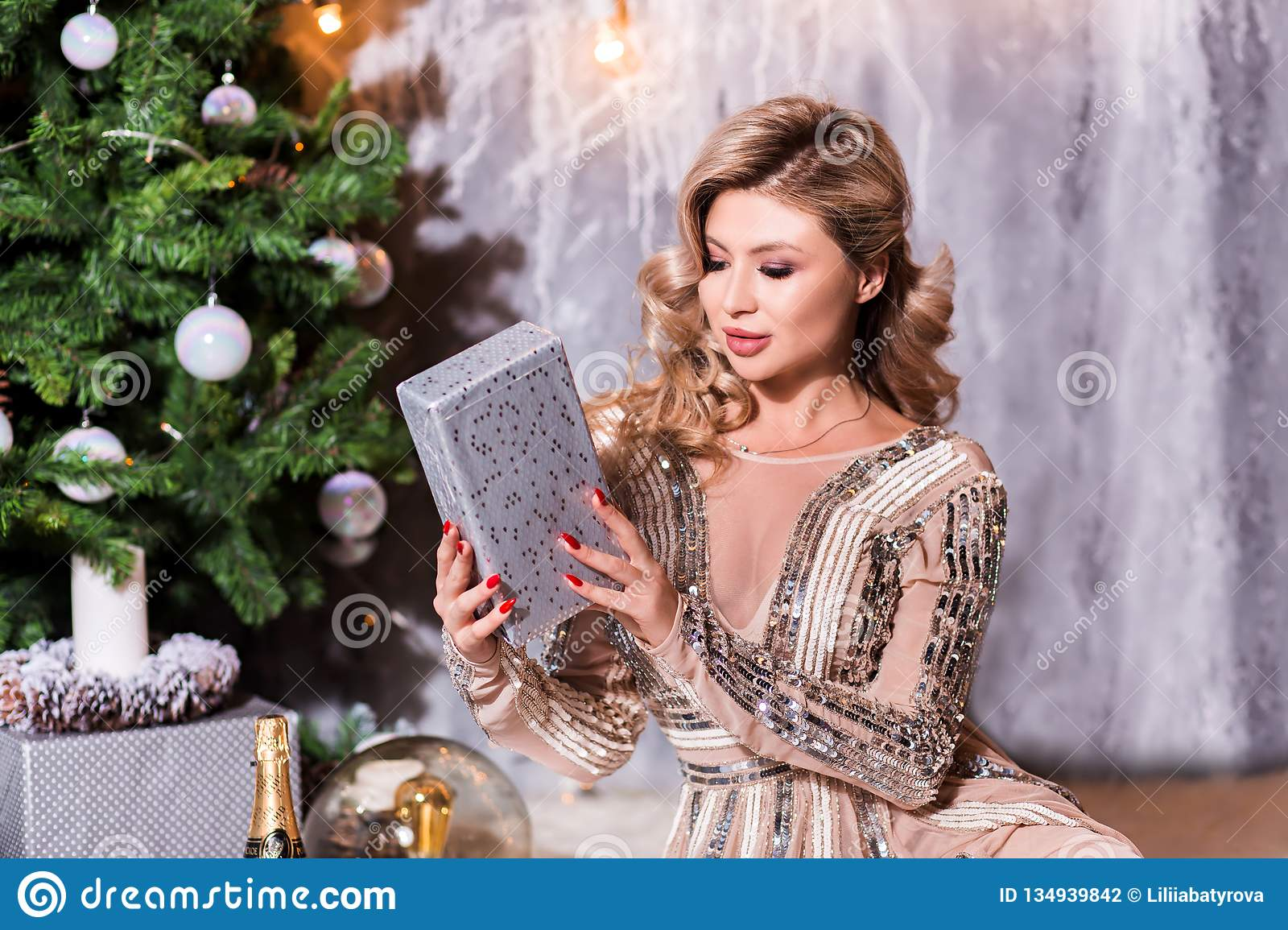 What a great surprise Beautiful young woman opening a gift box and smiling. fashion studio photo of beautiful charming woman with
