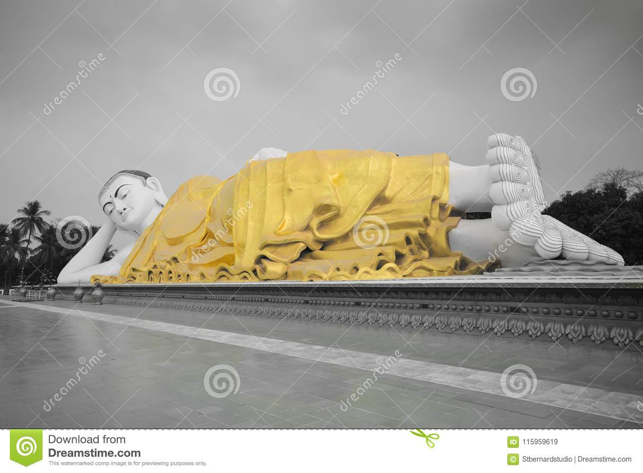 Full view of large Mya Tha Lyaung Reclining or sleeping Buddha in black and white with yellow robe