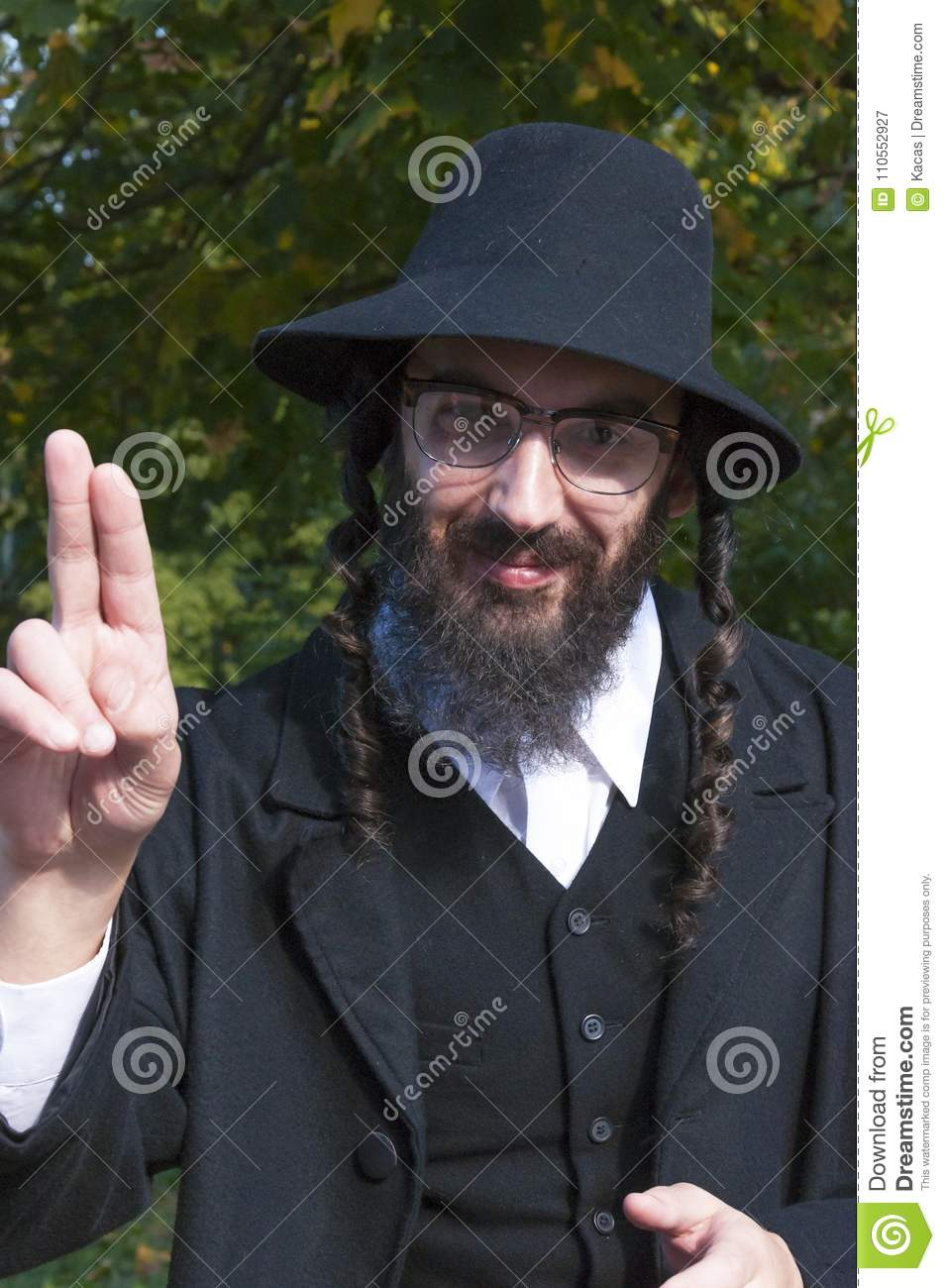 2aad6920565 Sunny outdoor portrait of a young smiling happy fingers blessing  traditional orthodox Jewish man with black beard and hat wearing eyeglasses
