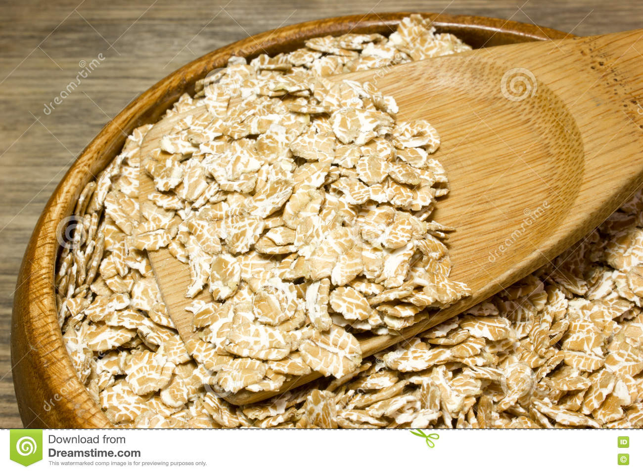 Wheat flakes in wooden spoon