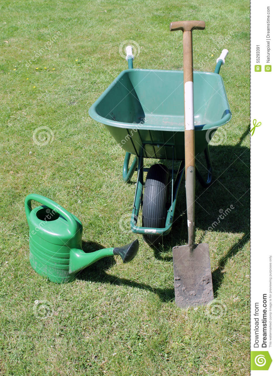 Wheel barrow shovel spade and watering can in the garden for Gardening tools watering