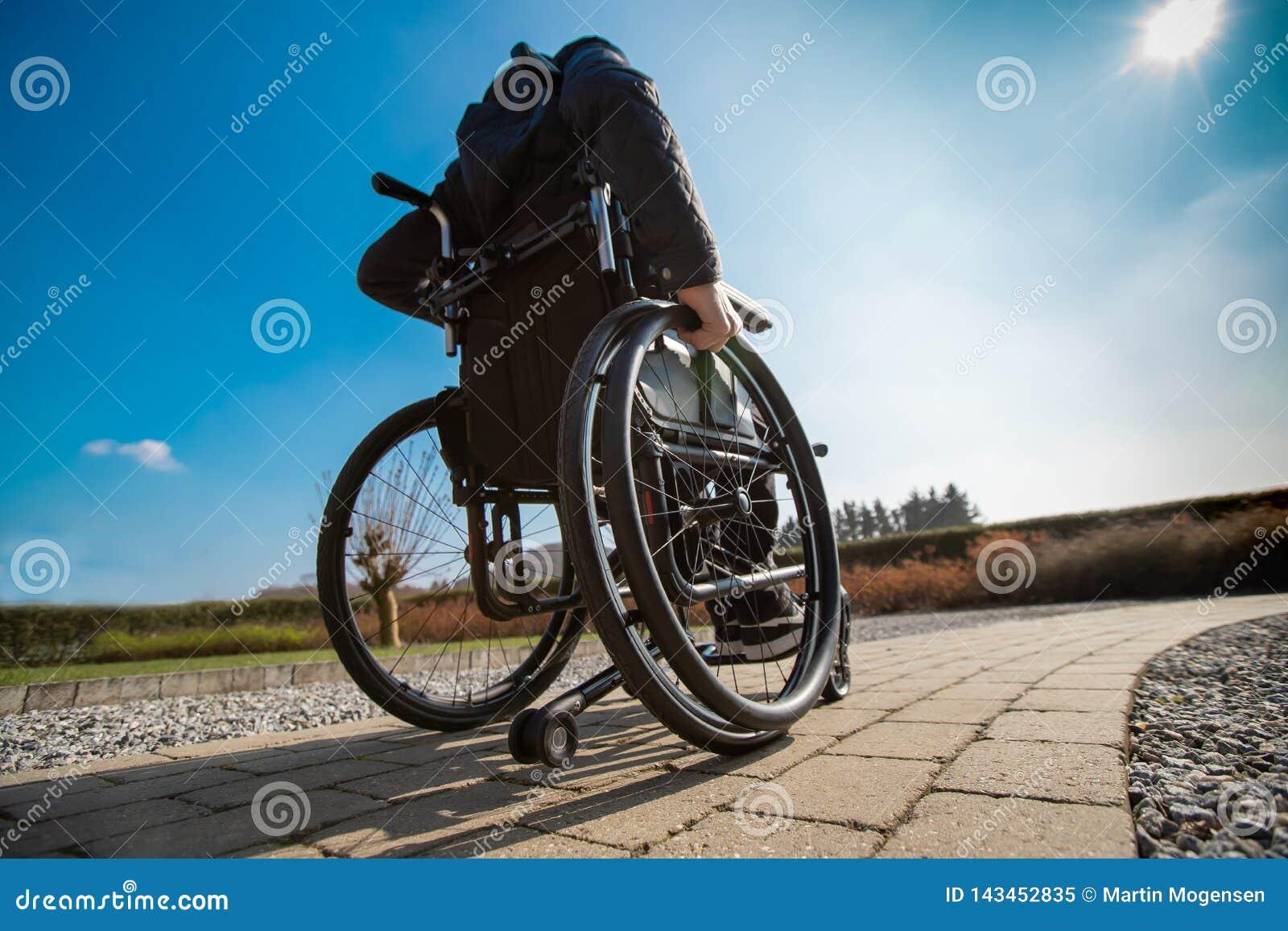 Wheelchar驾驶的废人在阳光下