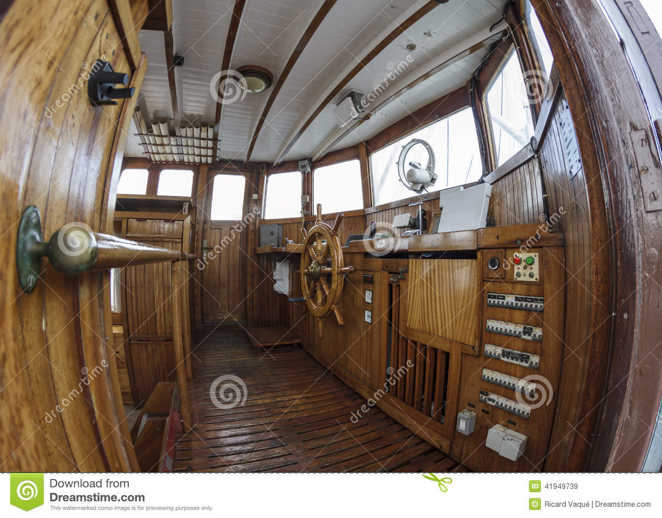 Wheelhouse, helm wheel and control panels in an old wooden boat. Point ...