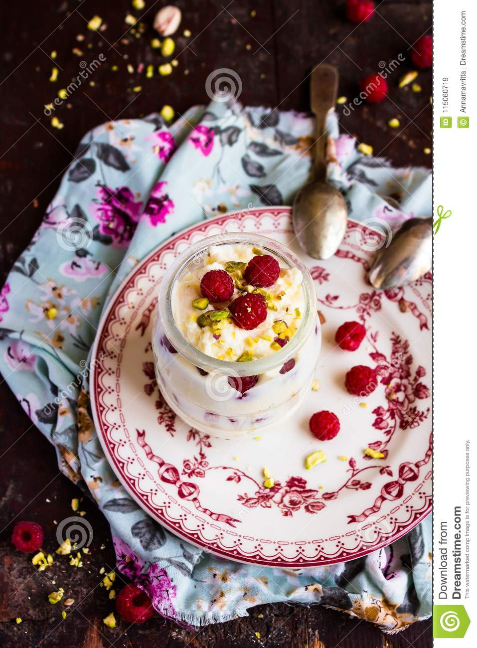 Whipped mascarpone cream cheese with white chocolate, fresh raspberry and pistachios in a jar, selective focus