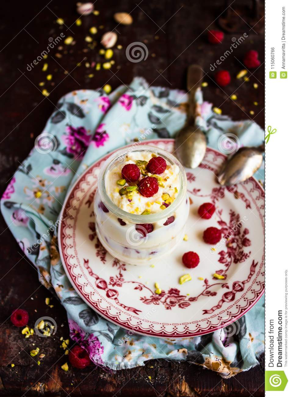 Whipped mascarpone cream cheese with white chocolate, fresh raspberry and pistachios in a jar