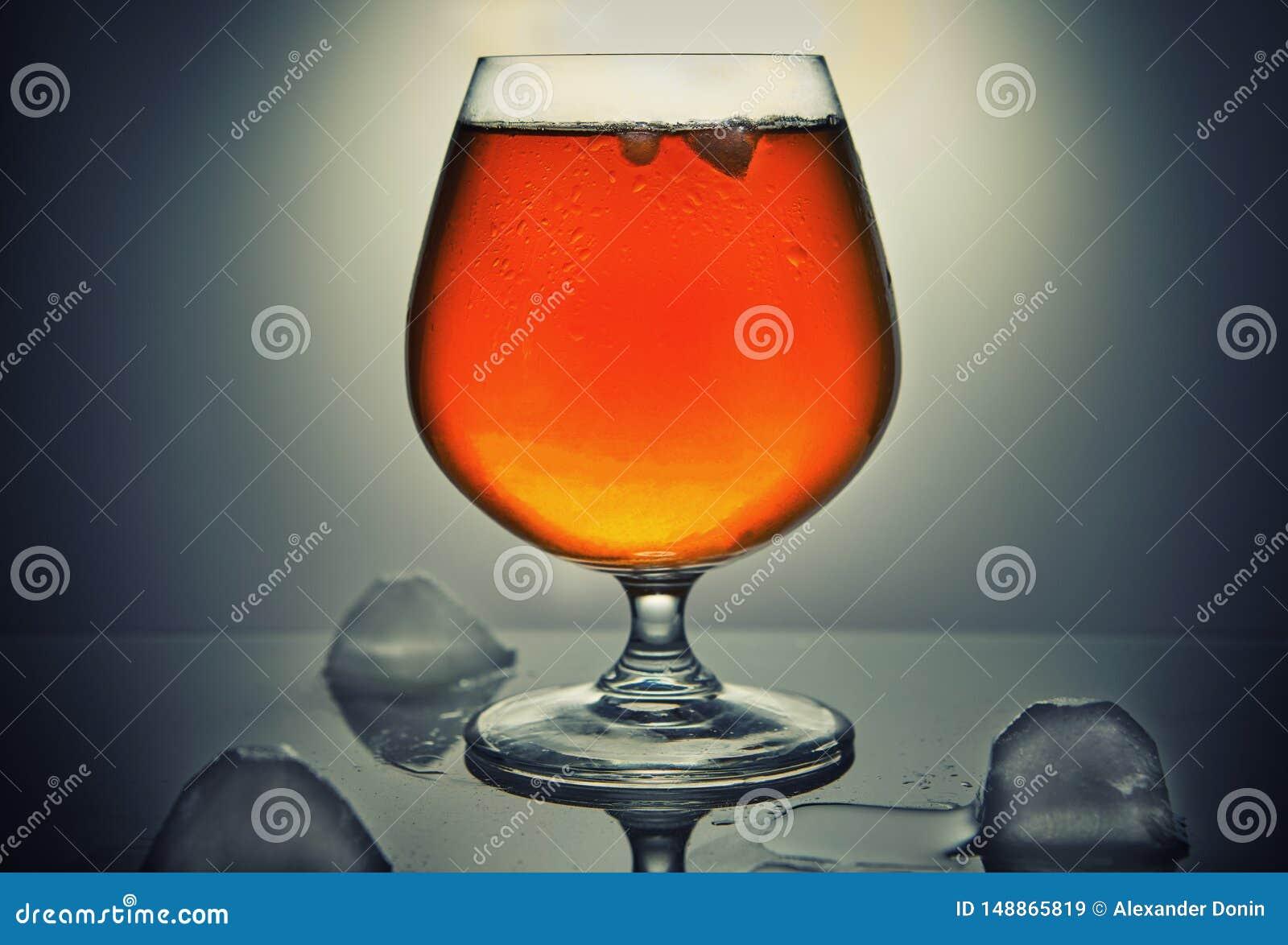 Whiskey, bourbon, eau-de-vie fine ou cognac avec de la glace sur un fond gris