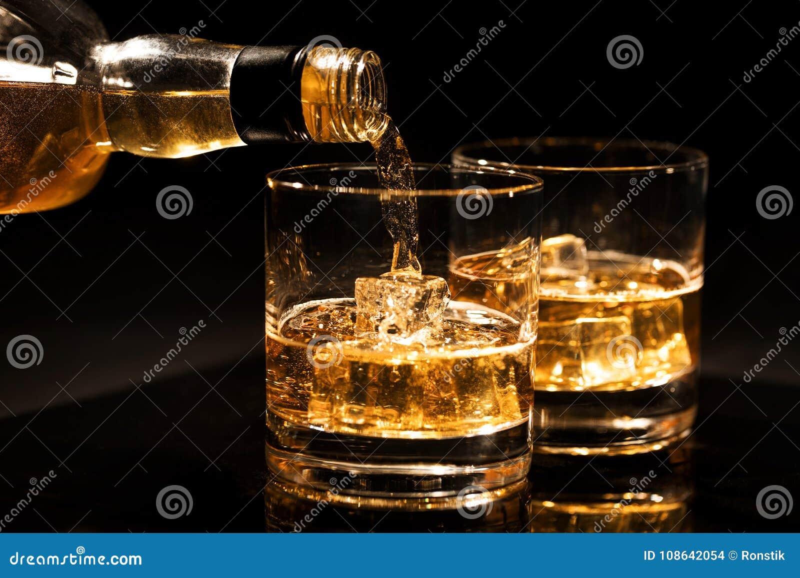 Whisky de colada en un vidrio de la botella con los cubos de hielo en negro