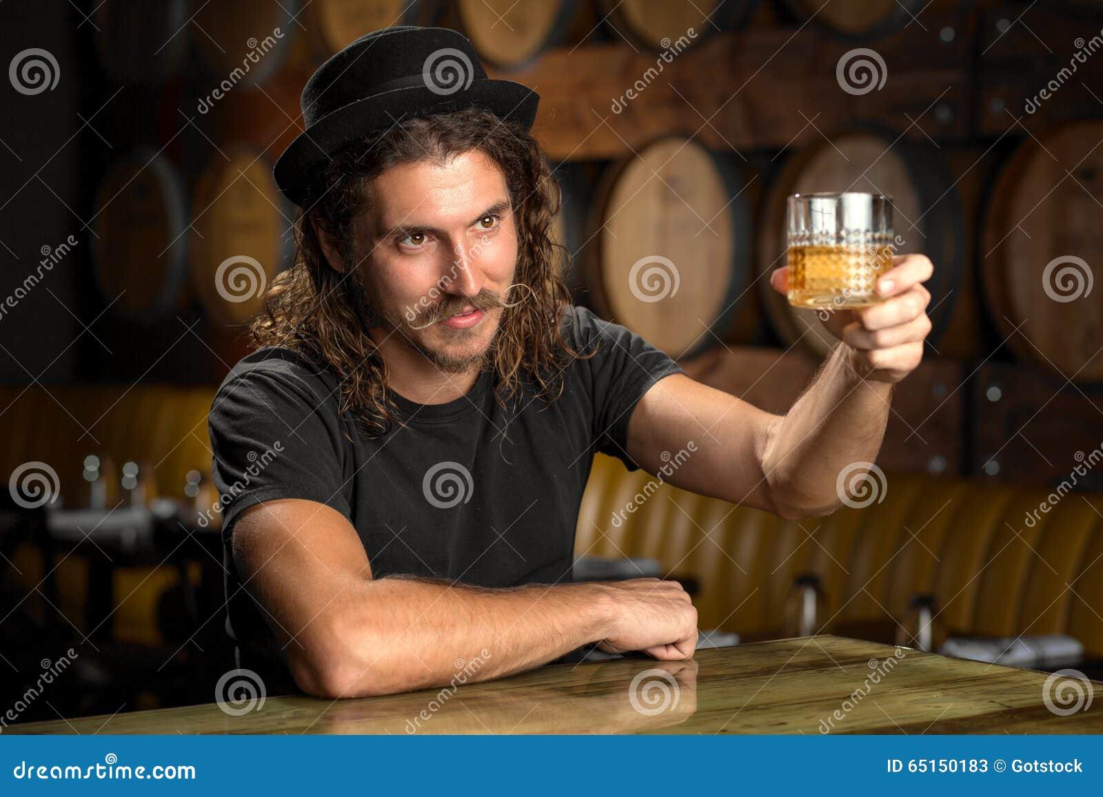 Whisky szkło rozwesela eleganckiego mężczyzna pije bourbon przy whisky destylarni restauraci barem