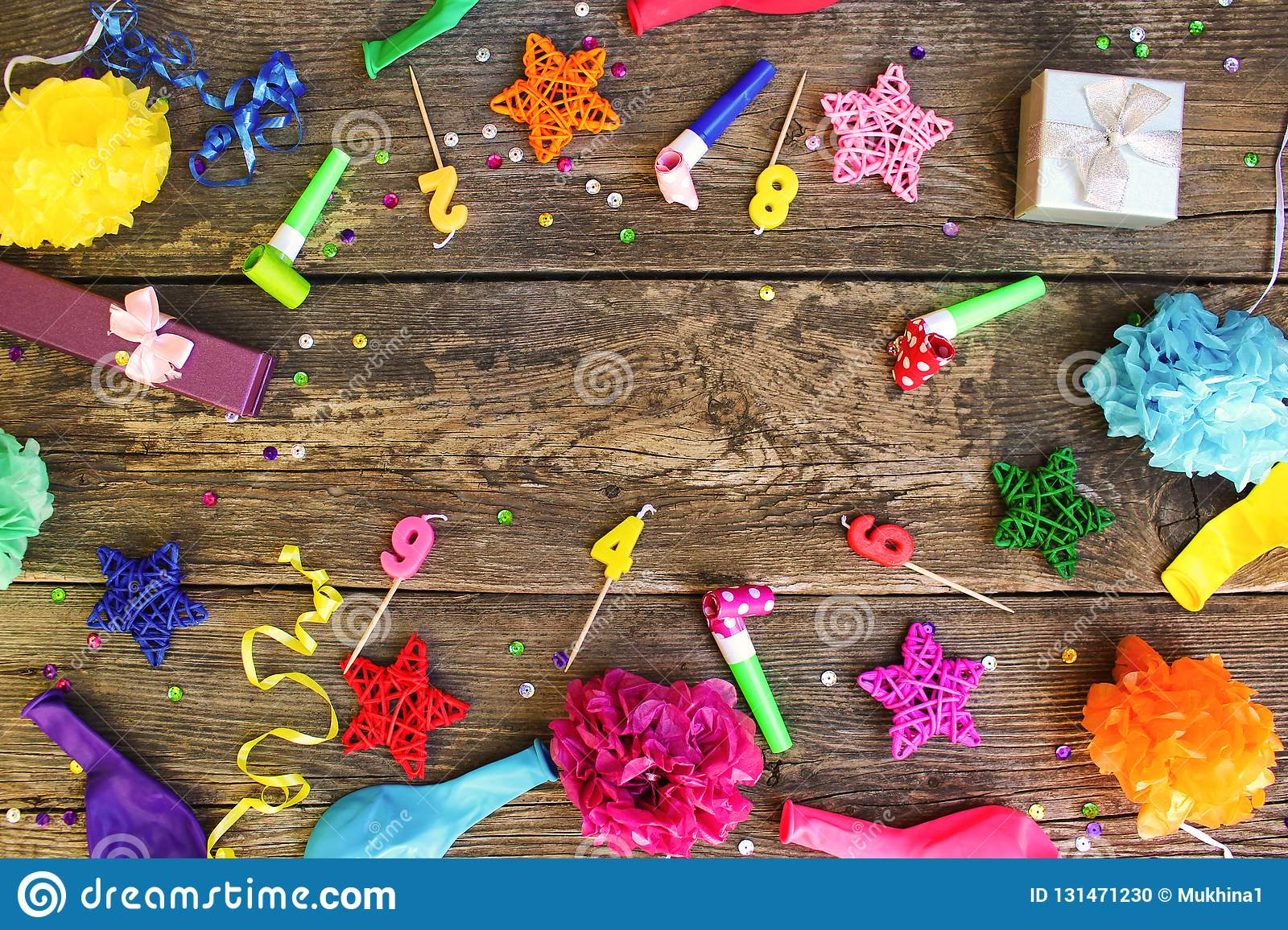 Whistles, balloons gifts, candles, decoration on old wooden background. Concept of children`s birthday party.