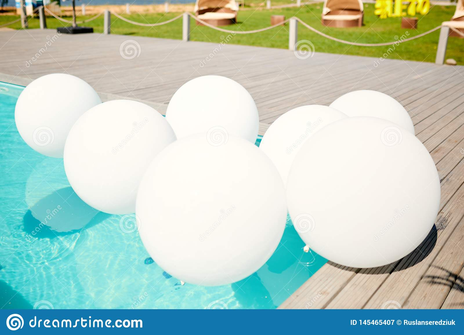 White balloons in the pool with clear water