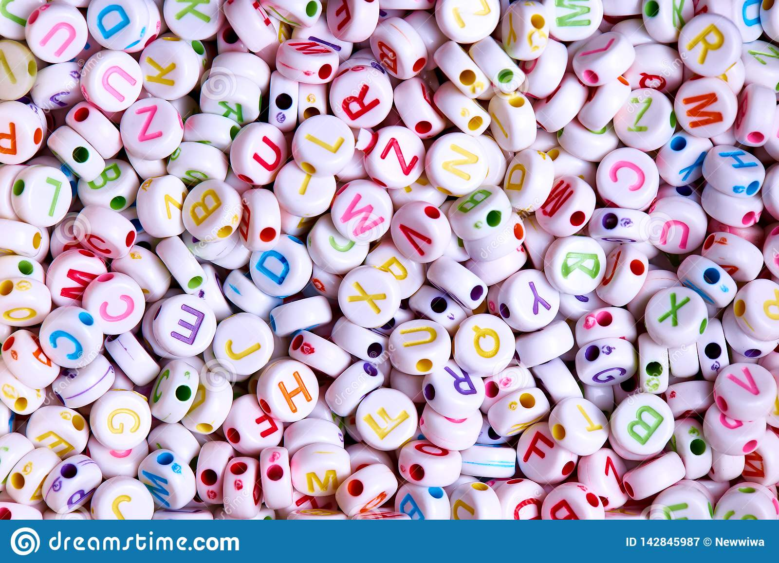 White beads with multicolored English letters close-up