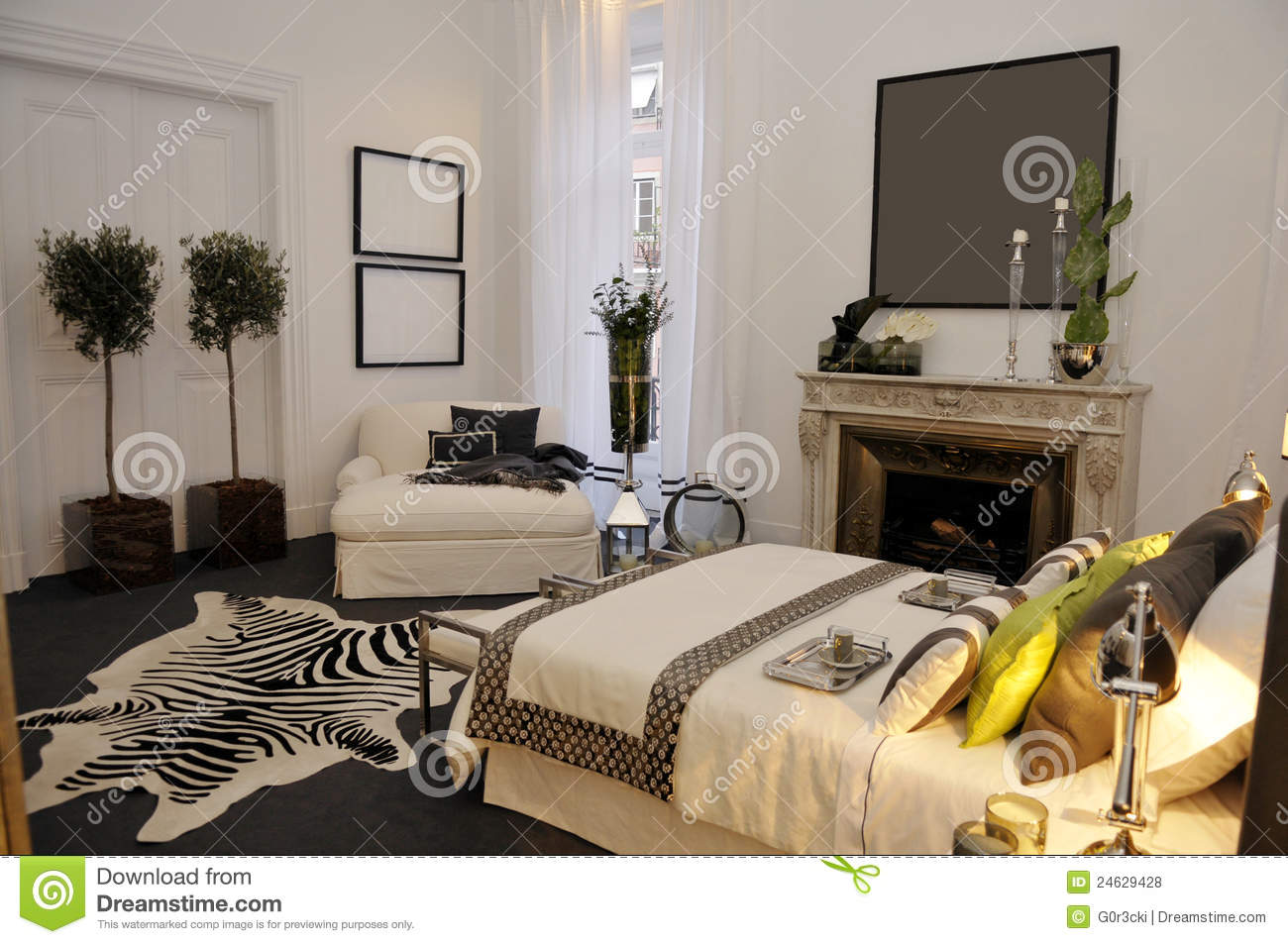 Warm inviting and modern bedroom with white tones and shades of black dark grey and green also with pillows and quilt