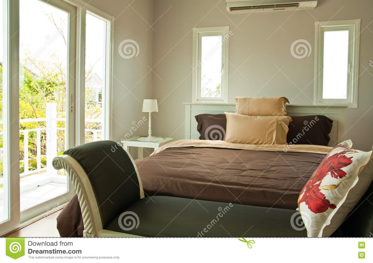white bedroom with brown sheet bed and couch stock images image