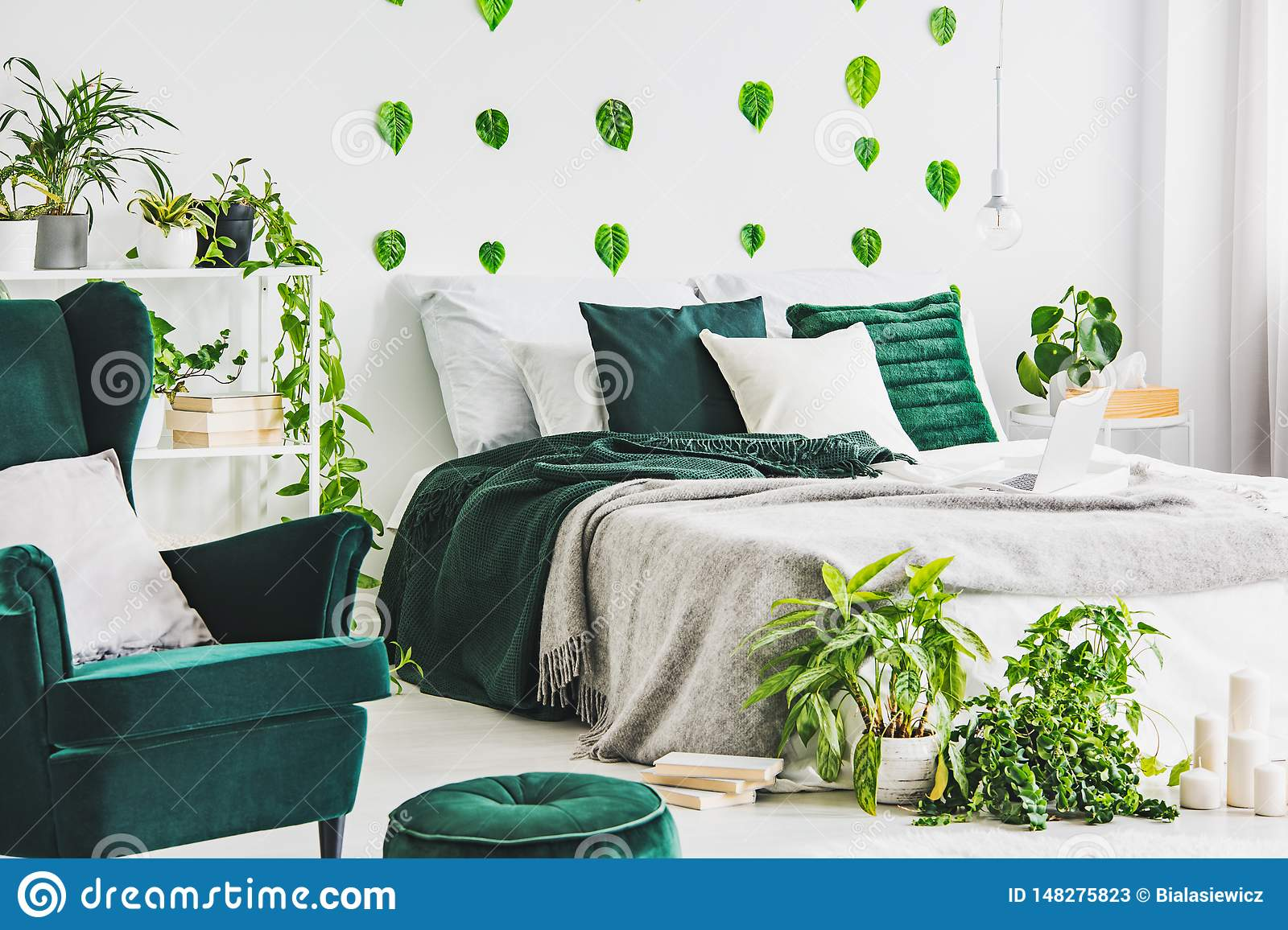 White bedroom interior with king size bed with grey nd emerald bedding, urban jungle and green leaf on the wall