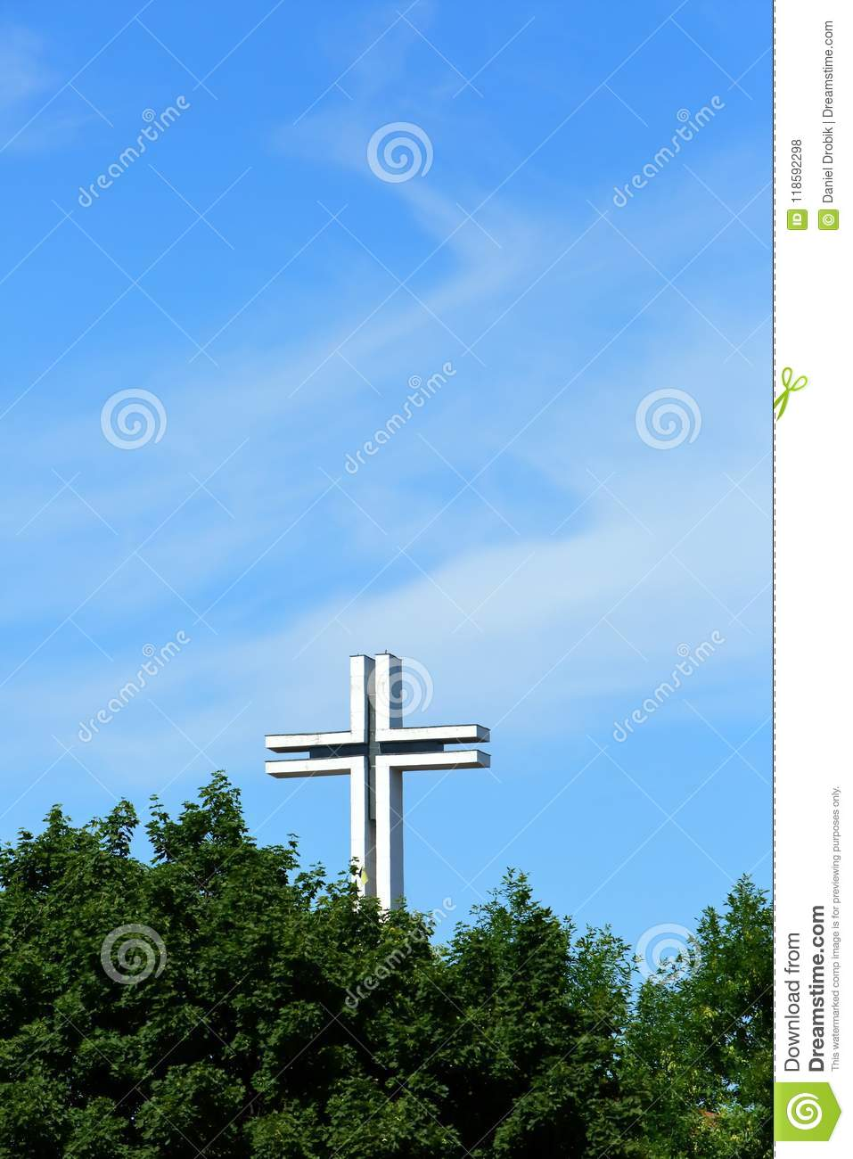 White Big Cross Against The Sky Shining Through Green Tree Crowns
