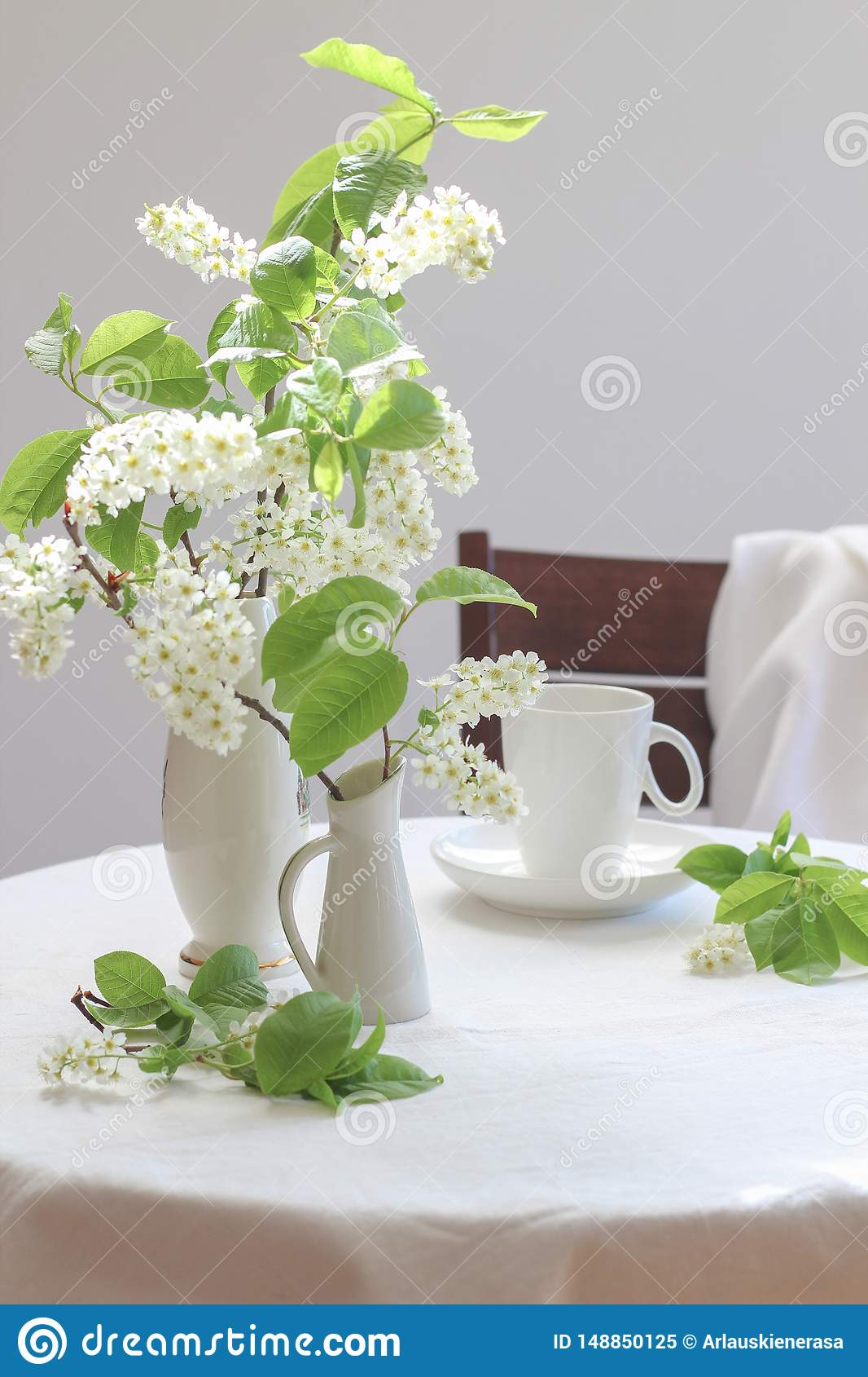 White bird cherry tree blooms in small vases and a cup of coffee on a white table