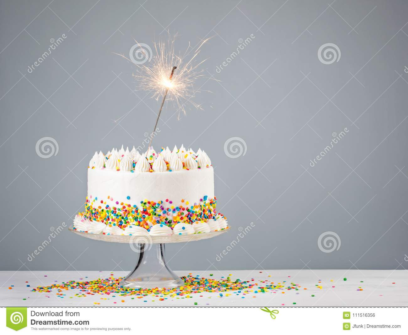White Birthday Cake With Colorful Sprinkles And Sparkler Over A Neutral Background