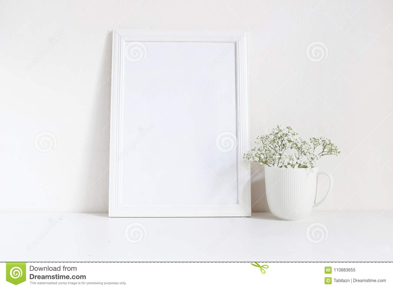 White blank wooden frame mockup with baby breath, Gypsophila flowers in porcelain mug on the table. Poster product