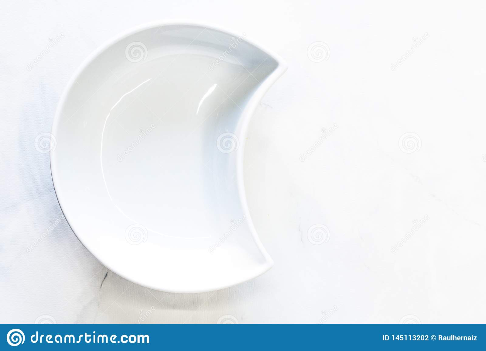 White bowl in the shape of a half-moon. Top view, space for text