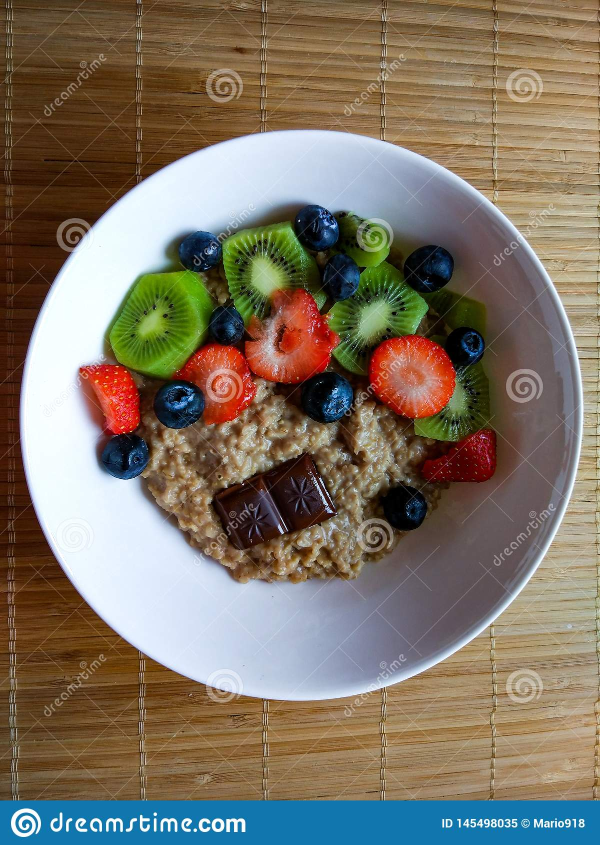 Breakfast bowl with strawberries, kiwi, blueberry with muesli and dark chocolate from above