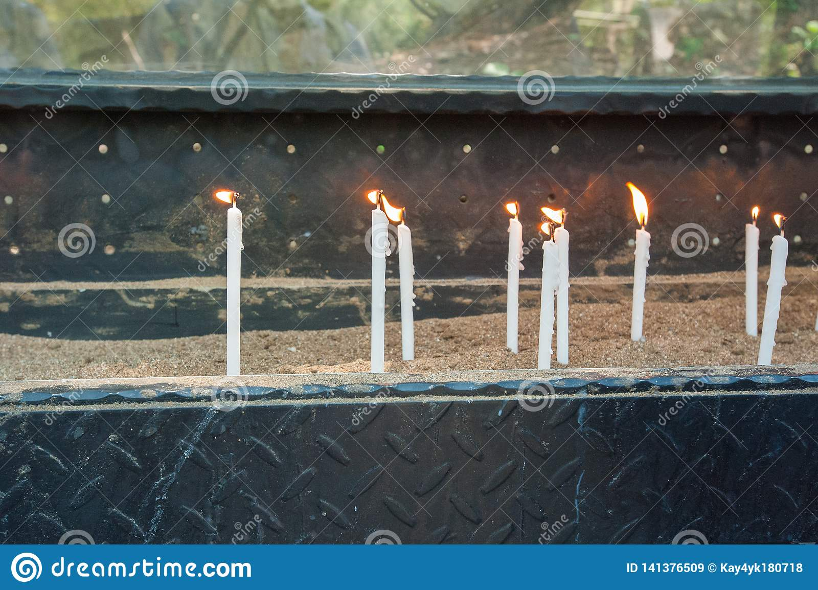 White burning candles stand on the sand