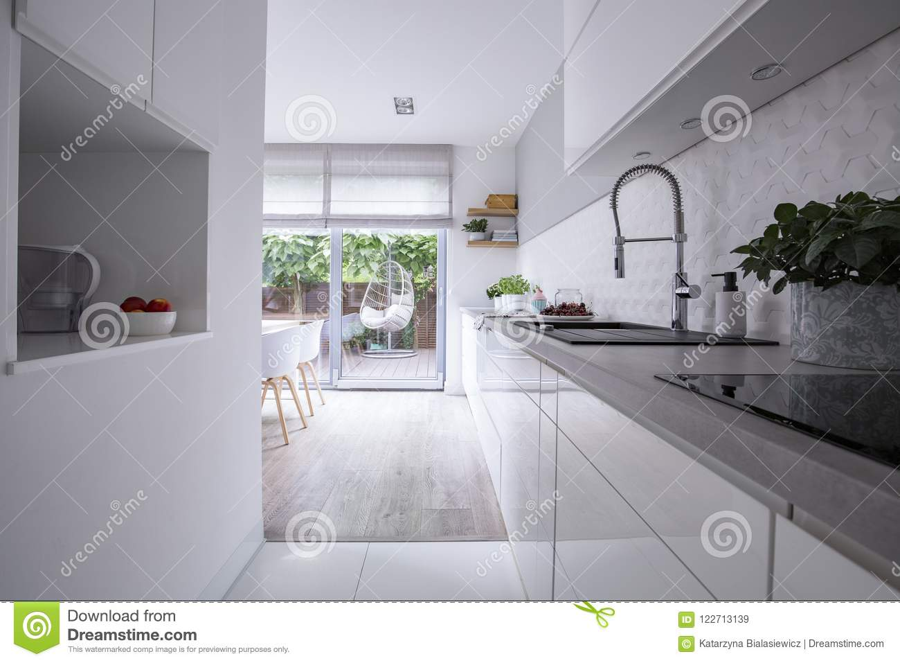 White cabinets in bright modern kitchen interior of house with terrace. Real photo