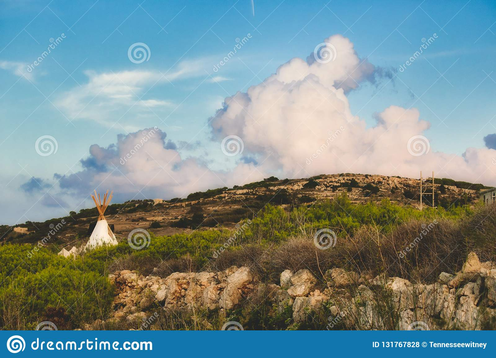 White canvas teepee camped in a field under a cloudy blue sky