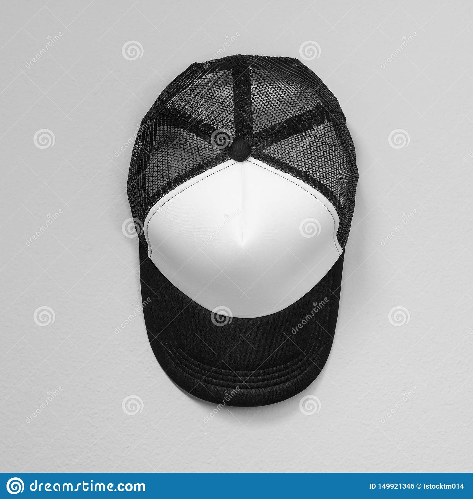 White caps with black nets on cement background. Top view angle of baseball cap