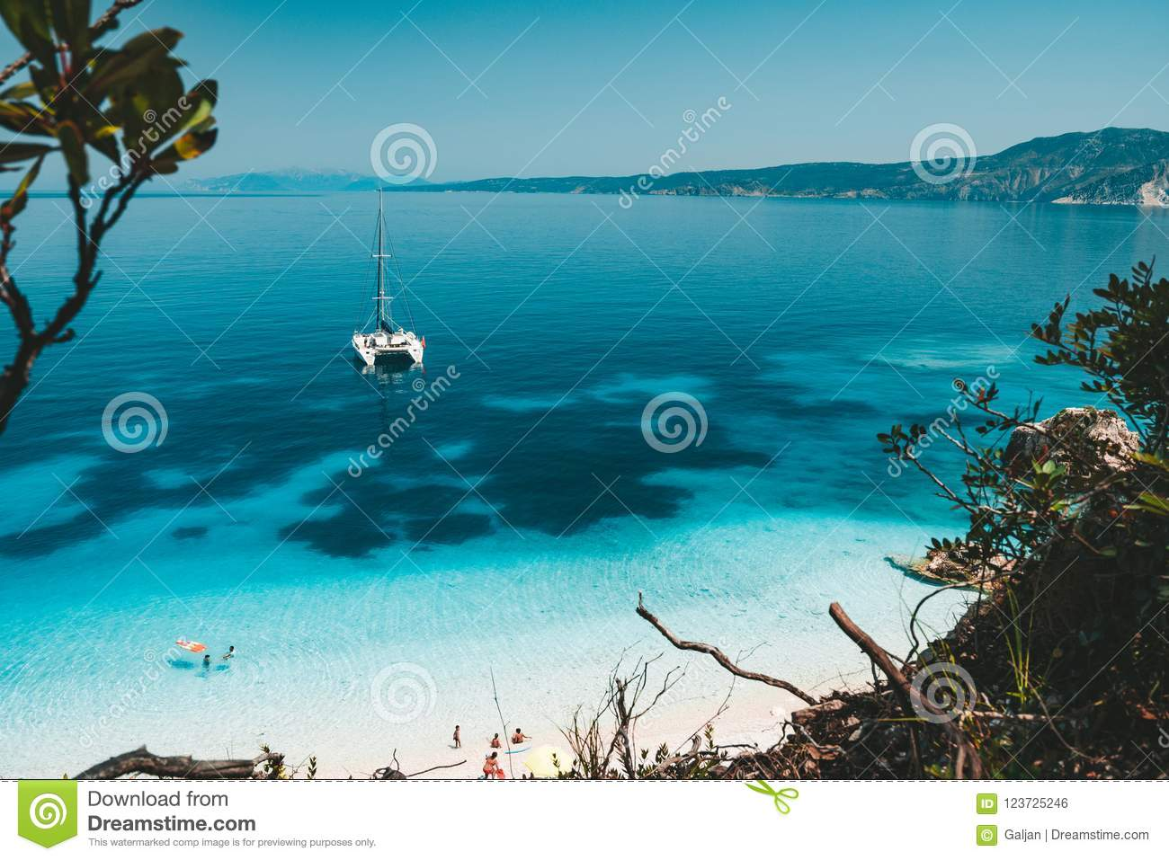White catamaran yacht at anchor on clear azure water surface in calm blue lagoon. Unrecognizable tourists leisure on the