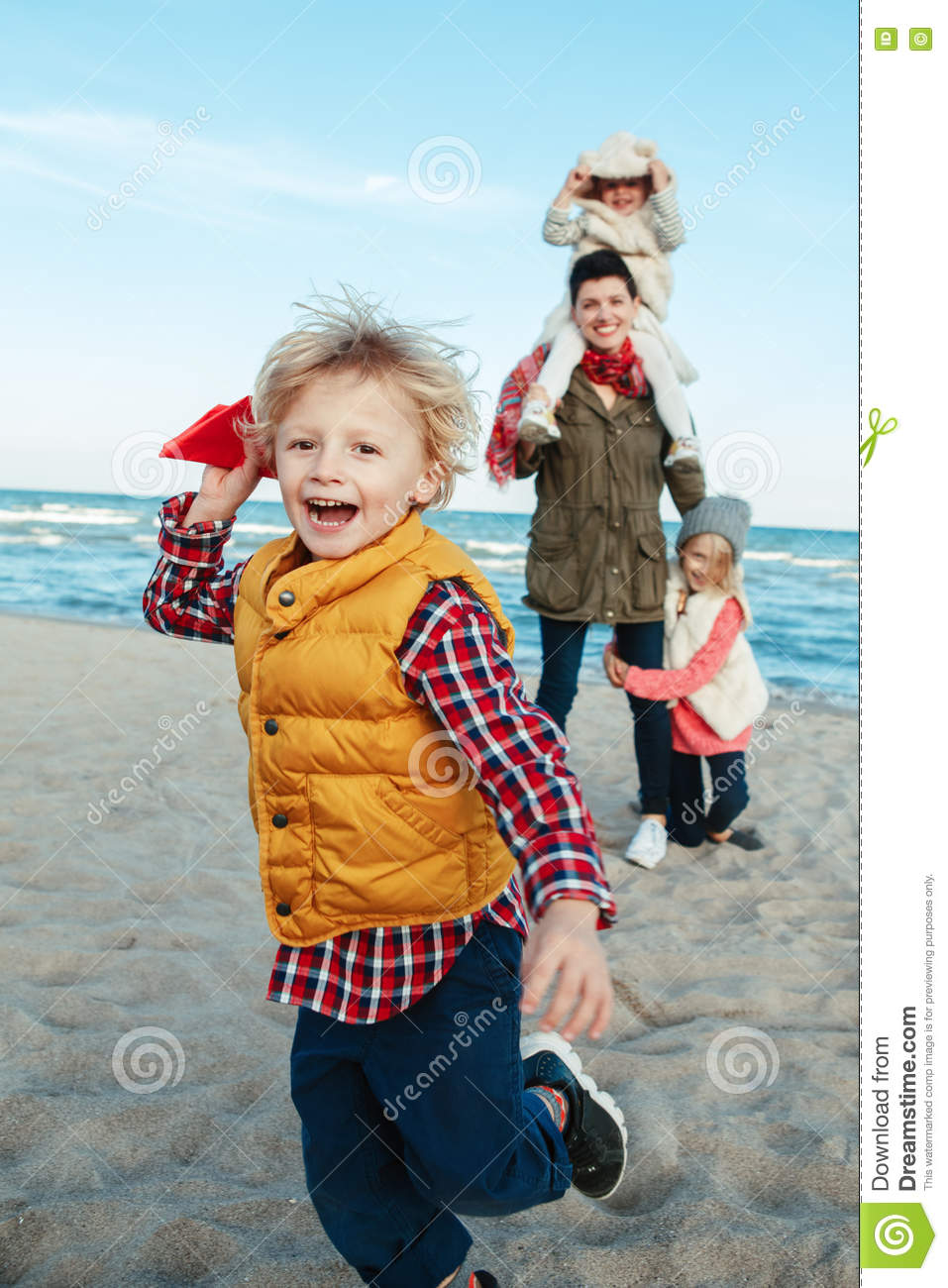 White Caucasian family, mother with three children kids playing paper planes, running on ocean sea beach on sunset outdoors