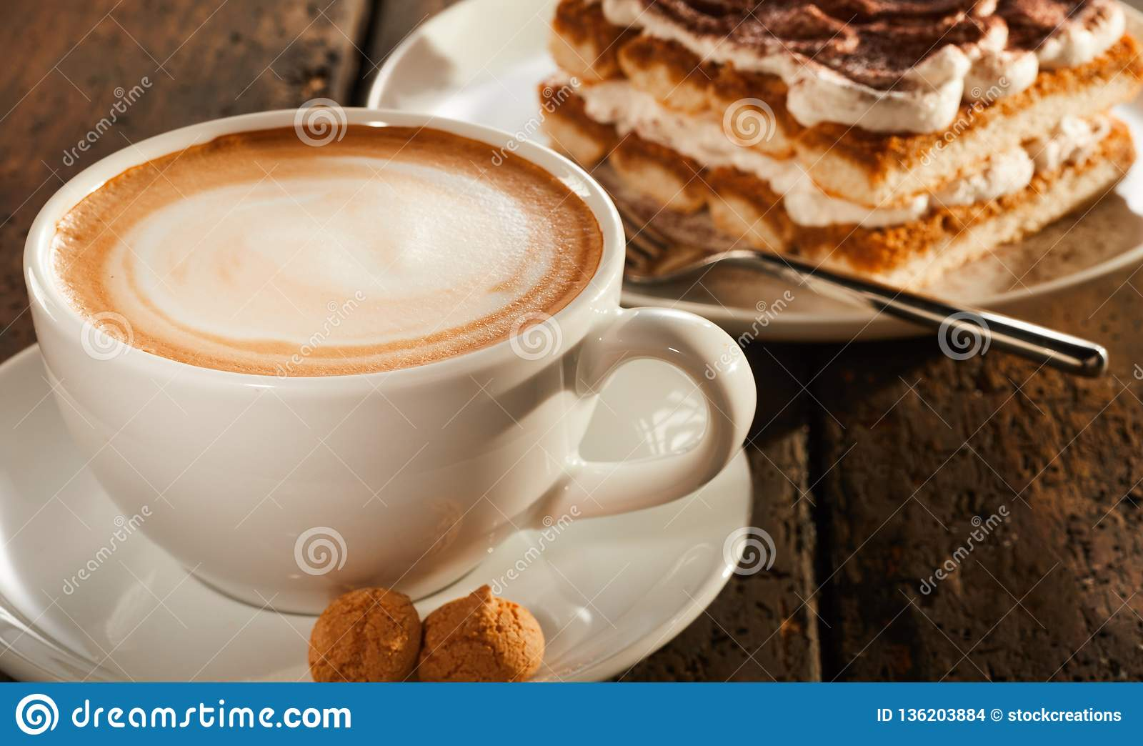 White ceramic cup of coffee with dessert