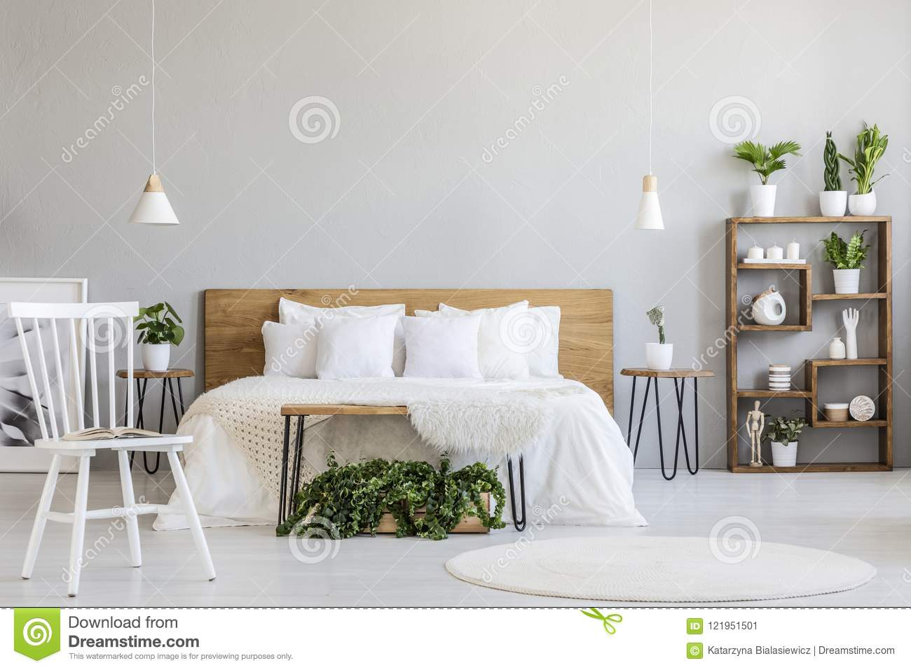 White Chair Near Bed With Wooden Headboard In Bright Bedroom Int ...