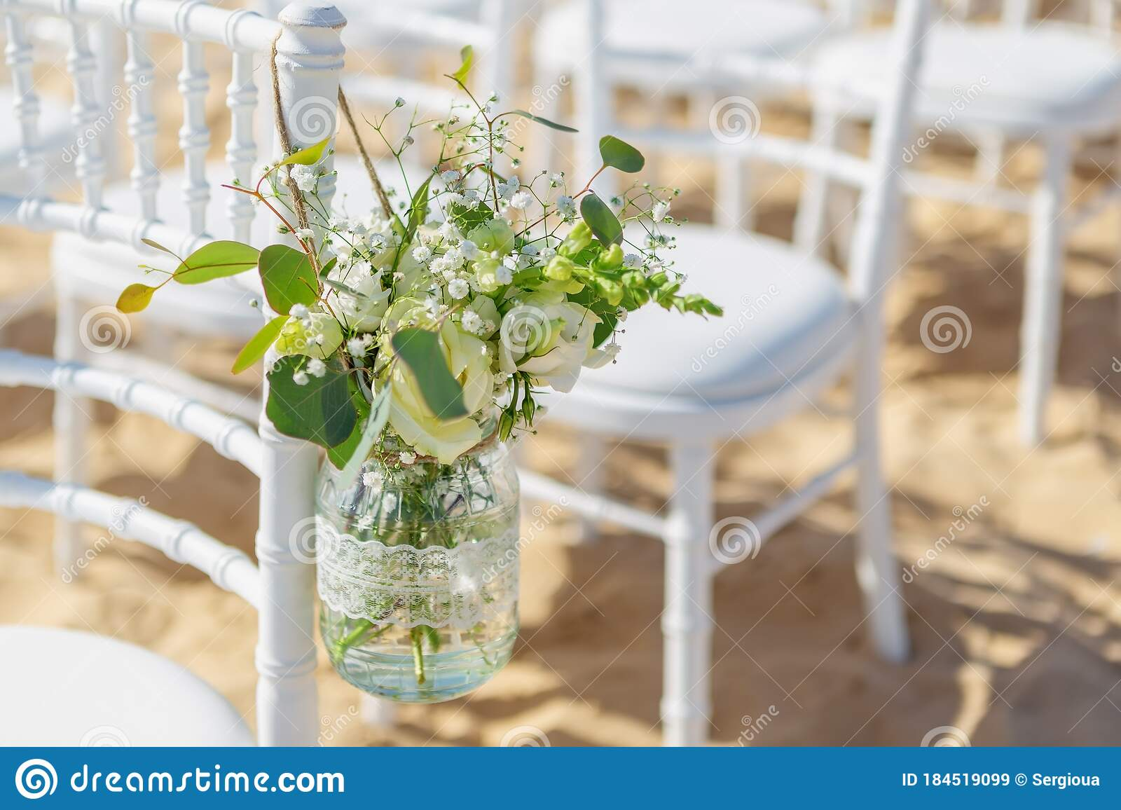 White Chairs At A Beach Wedding Ceremony Decorated With A Hanging Jar Of Flowers On A Sunny Day Close Up Stock Image Image Of Empty Celebrate 184519099
