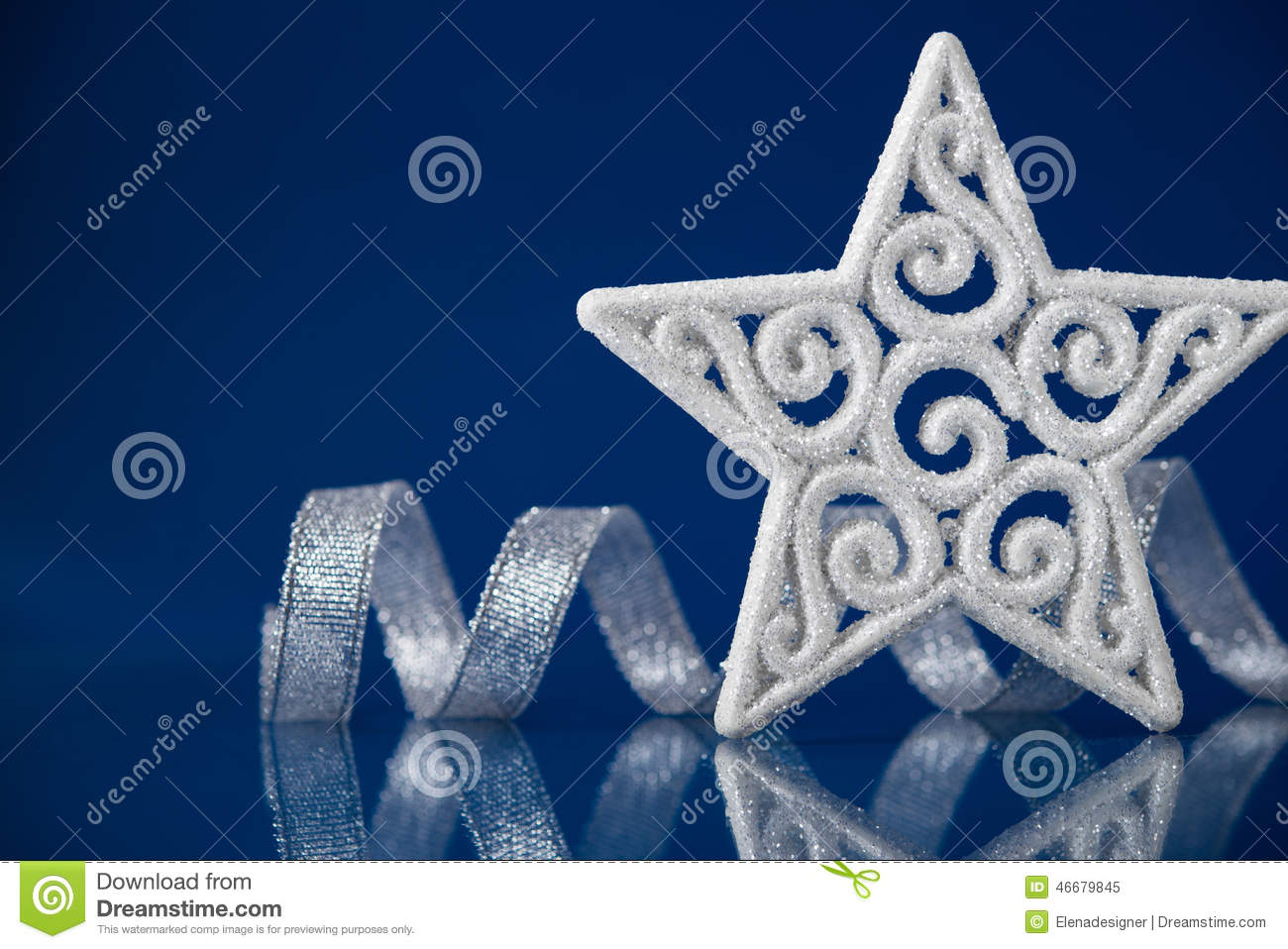 White Christmas Star With Silver Ribbon On Blue Background With