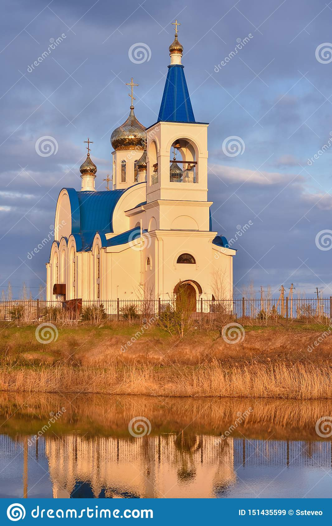 White church with blue roof on lake