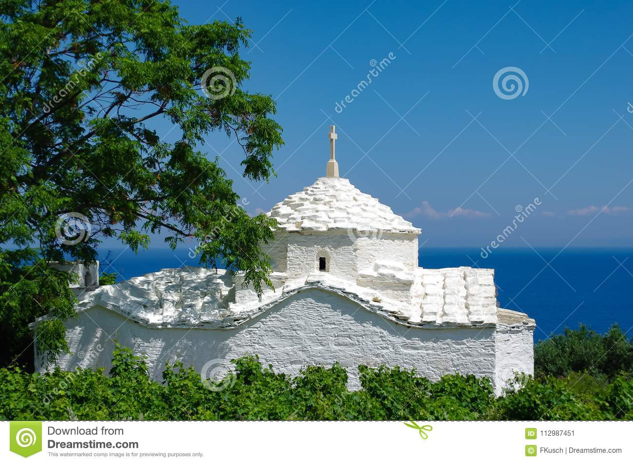 White church in front of the blue sea, framed by bushes and a tree, Samos, Greece