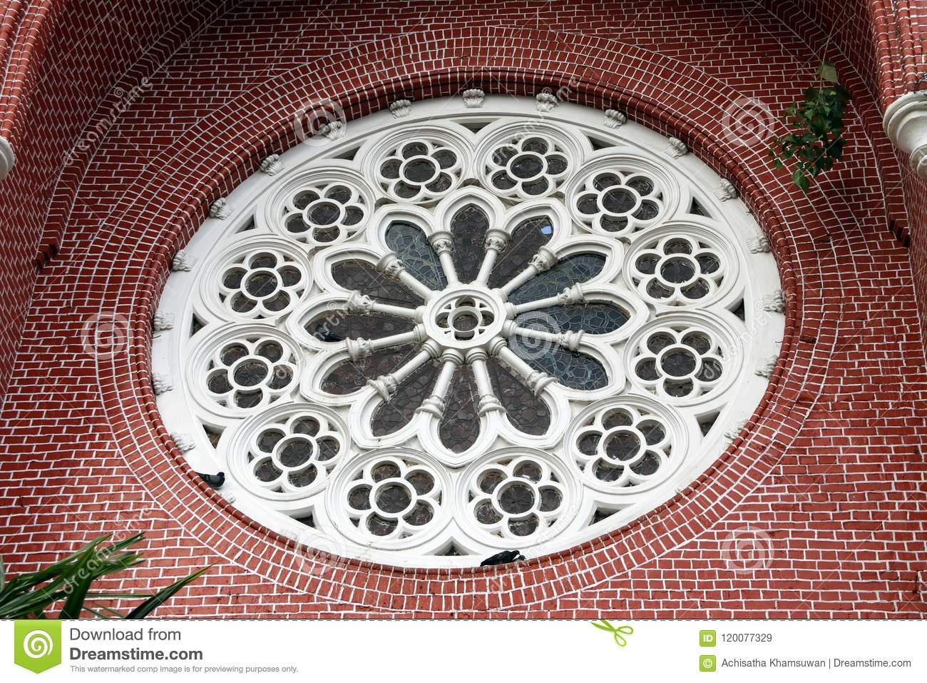 White Circle Mortar flower pattern with Stained Glass and red brick of exterior of church gable at cathedral of the holy trinity.